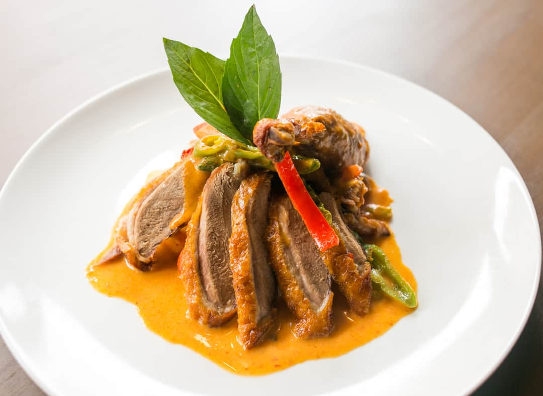 Thai Holic sliced duck dish served with chef's special sauce, red bell pepper, and green bell pepper